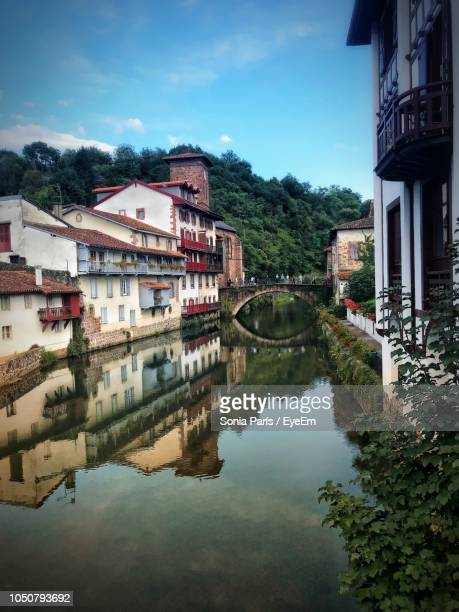 reflection of buildings in lake against sky - saint jean pied de port stock photos and pictures