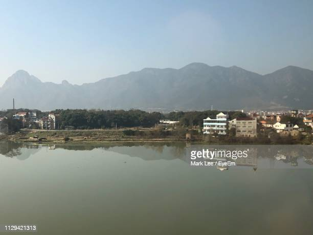 reflection of buildings in lake against sky - mark's stock pictures, royalty-free photos & images