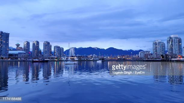 reflection of buildings in lake against sky - waterfront stock pictures, royalty-free photos & images