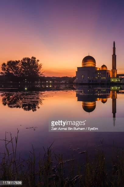 reflection of buildings in lake at sunset - floating mosque stock pictures, royalty-free photos & images