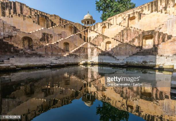 reflection of buildings in lake - abhaneri stock photos and pictures