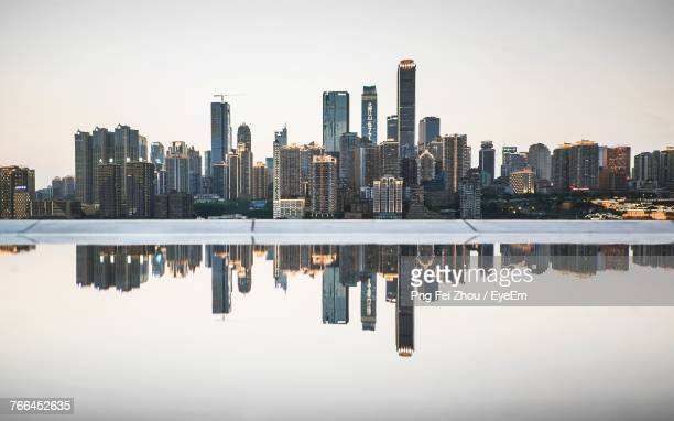 reflection of buildings in lake - chongqing stock photos and pictures