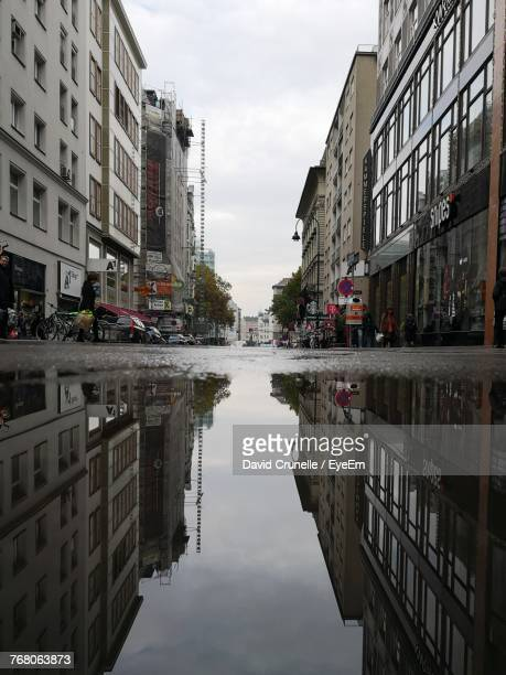 reflection of buildings in puddle on street - puddle stock pictures, royalty-free photos & images