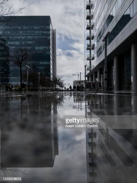 reflection of buildings in puddle - noam cohen stock pictures, royalty-free photos & images