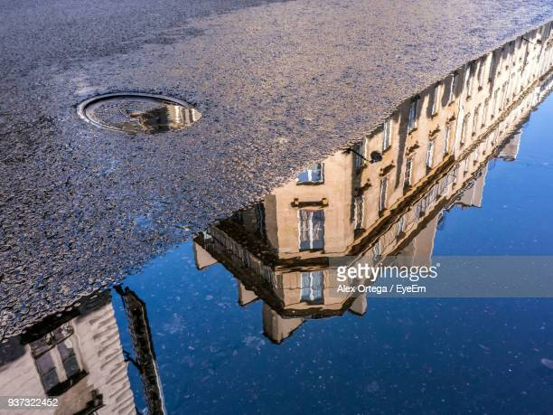 reflection of buildings in puddle - puddle stock pictures, royalty-free photos & images