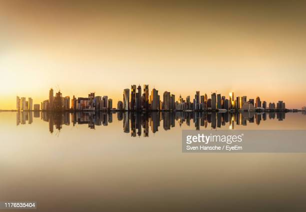 reflection of buildings in river against sky during sunset - qatar stock pictures, royalty-free photos & images