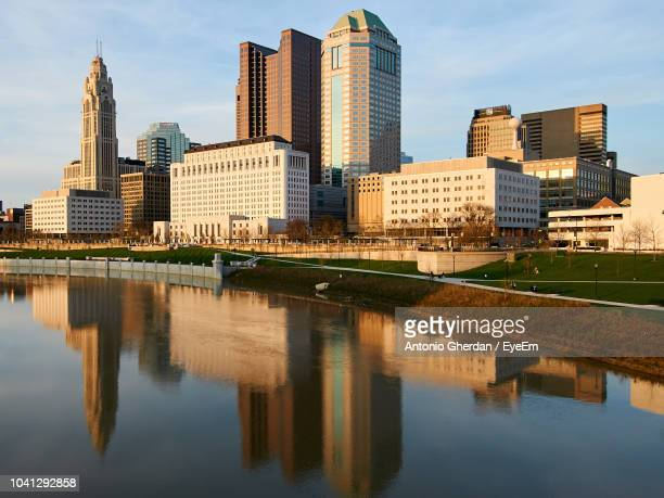 reflection of buildings in river against sky - columbus ohio stock photos and pictures
