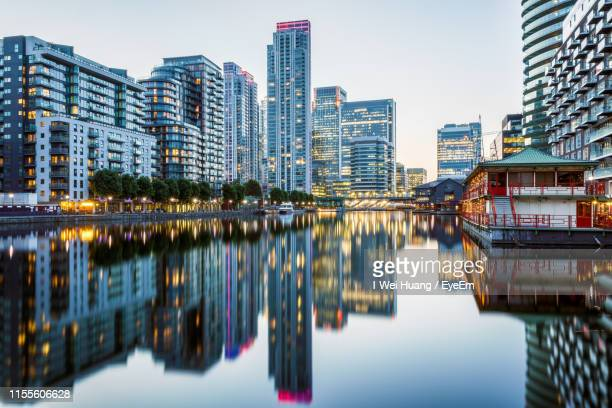 reflection of buildings in river against sky - canary wharf stock pictures, royalty-free photos & images