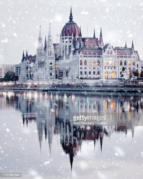 reflection of buildings in river during snowfall - budapest stock-fotos und bilder