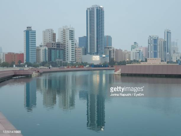 reflection of buildings in sea side against sky in city - bahrain stock-fotos und bilder
