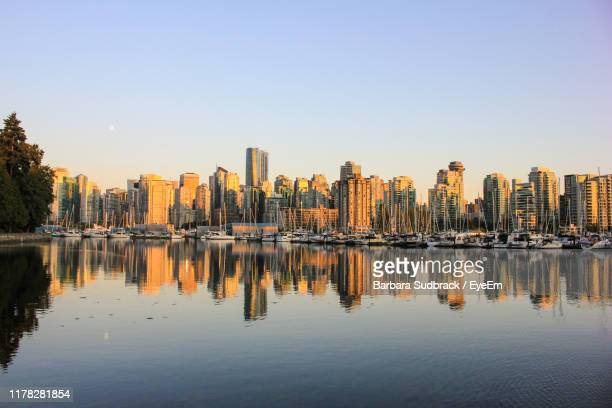 reflection of buildings in water against clear sky - vancouver skyline stock pictures, royalty-free photos & images