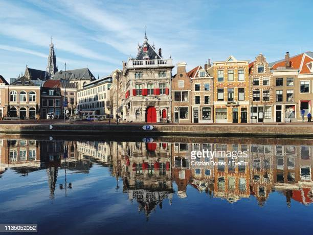 reflection of buildings in water - haarlem stock photos and pictures