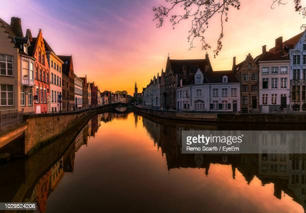 reflection of buildings on canal in city during sunset - bruges stock pictures, royalty-free photos & images
