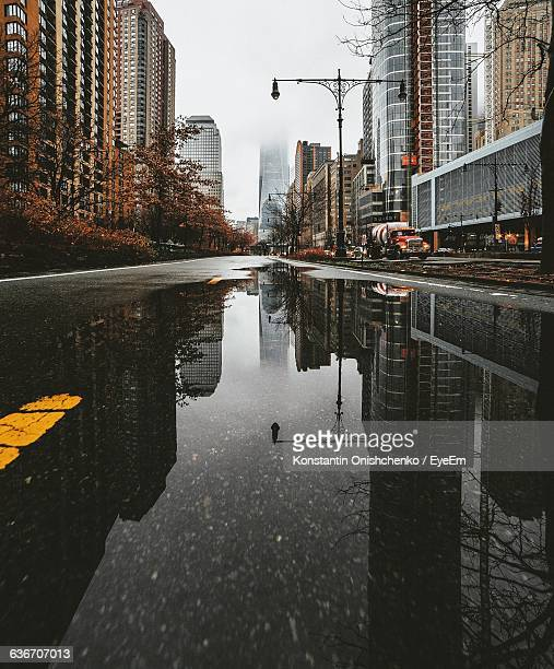 reflection of buildings on puddle at manhattan - puddle stock pictures, royalty-free photos & images