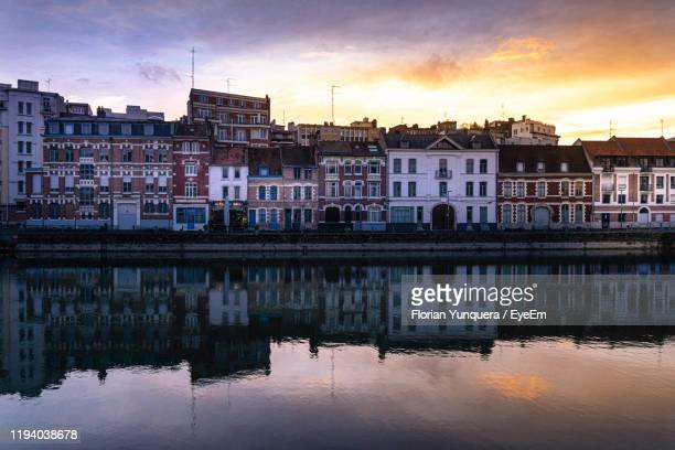 reflection of buildings on river against sky at sunset - lille stock pictures, royalty-free photos & images
