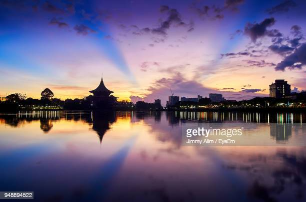reflection of buildings on river against sky during sunset - sarawak state stock pictures, royalty-free photos & images