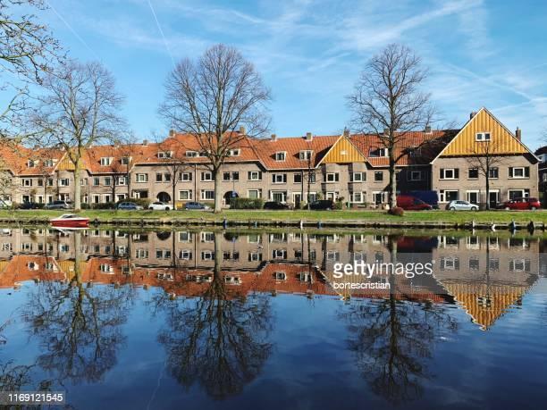 reflection of buildings on river against sky - bortes stock-fotos und bilder