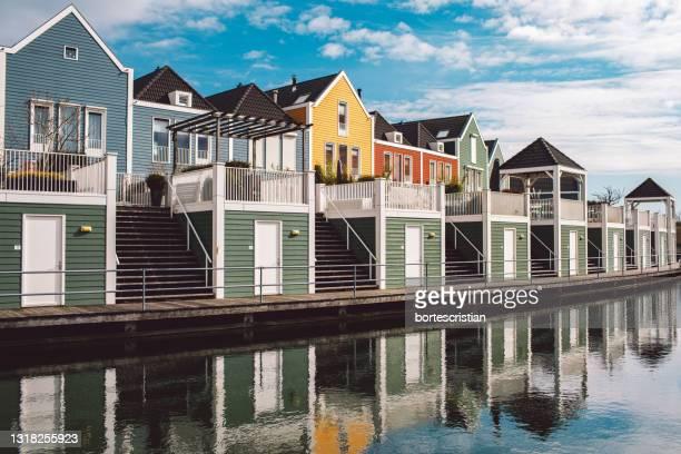 reflection of buildings on river against sky - bortes foto e immagini stock