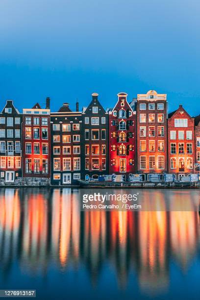 reflection of buildings on water against blue sky - amsterdam stock-fotos und bilder