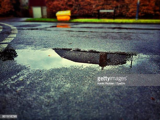 Reflection of built structure and clouds in puddle