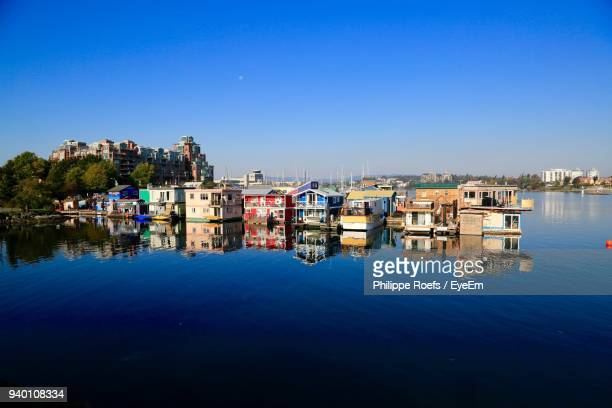 reflection of built structure in lake against clear blue sky - vancouver island stockfoto's en -beelden
