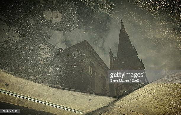 reflection of built structure in puddle - steve matten stock pictures, royalty-free photos & images