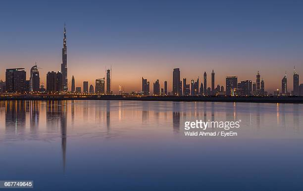 Reflection Of Burj Khalifa And Modern Building In Sea At Sunset