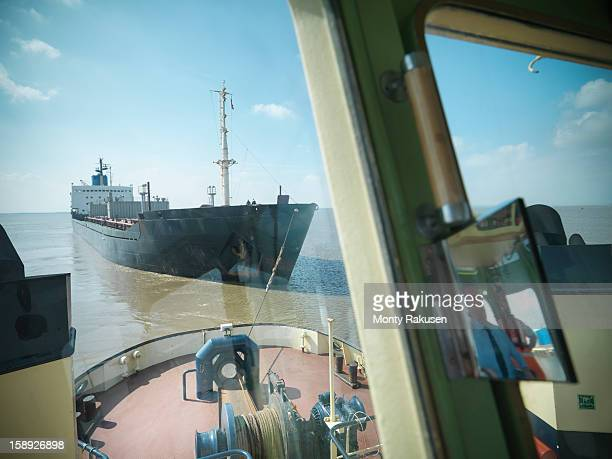 Reflection of captain in bridge of tugboat towing ship at sea