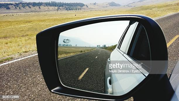 Reflection Of Car And Road On Side-View Mirror