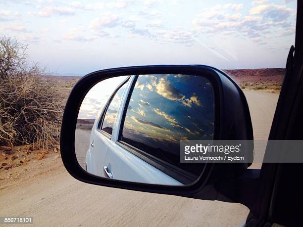 Reflection Of Car On Side-View Mirror Against Sky