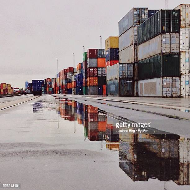 Reflection Of Cargo Containers On Puddle