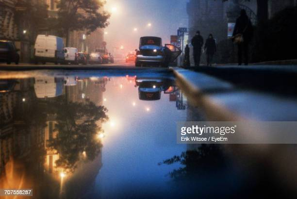 Reflection Of Cars In City On Puddle