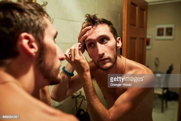 Reflection of Caucasian man plucking eyebrow in mirror