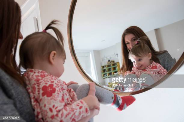 reflection of caucasian mother and baby daughter in mirror - girl in mirror stock photos and pictures