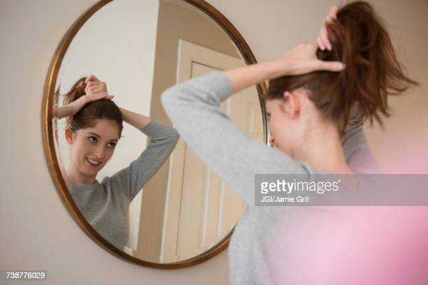 Reflection of Caucasian woman in mirror pulling back hair