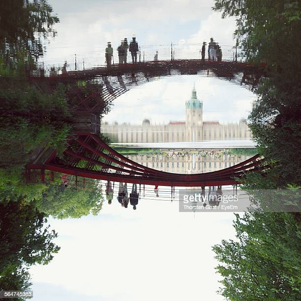 Reflection Of Charlottenburg Palace And People On Arch Bridge On Pond