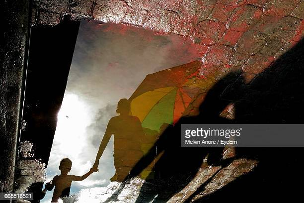 Reflection Of Child With Parent On Puddle