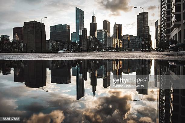 Reflection Of City Building On Puddle In Street