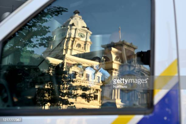 A reflection of City Hall is seen in the window of a police van and protestors are seen through the vehicle in Philadelphia PA on May 30 2020...