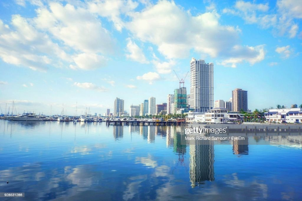 Reflection Of City In Water Against Sky : Stock Photo