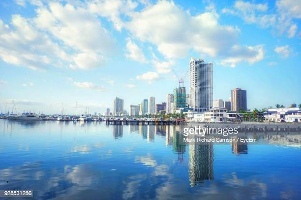 reflection of city in water against sky - manila philippines stock pictures, royalty-free photos & images
