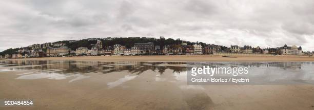 reflection of cityscape in sea against cloudy sky - trouville sur mer stock pictures, royalty-free photos & images