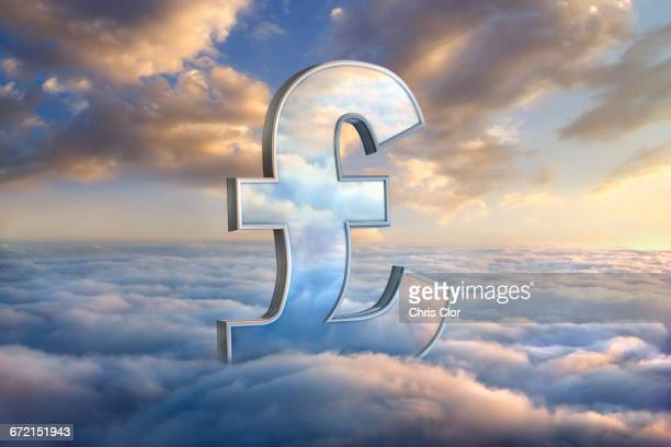 Reflection of clouds in British pound symbol in sky