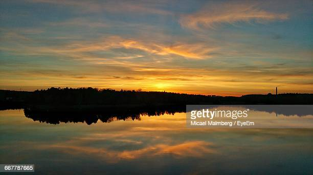 Reflection Of Clouds In Calm Lake At Sunset