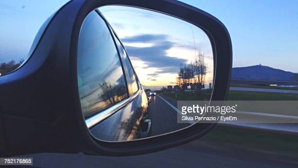 reflection of clouds in side-view mirror - vehicle mirror stock photos and pictures