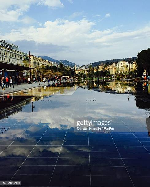 Reflection Of Cloudy Blue Sky On Wet Tiled Floor In City