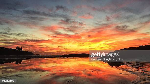 Reflection Of Cloudy Orange Sky In River During Sunset