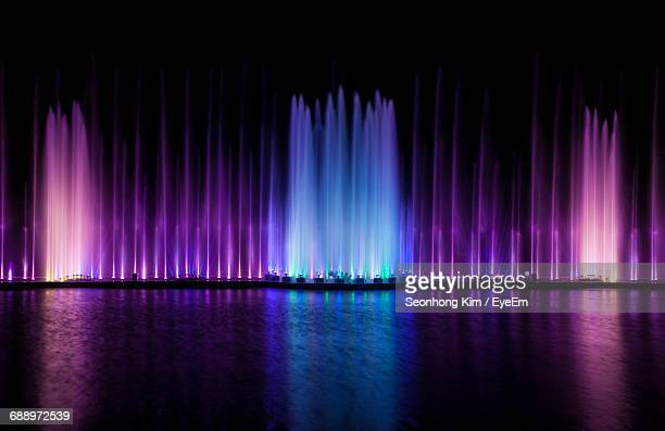 reflection of colorful lights in water - fountain stock pictures, royalty-free photos & images