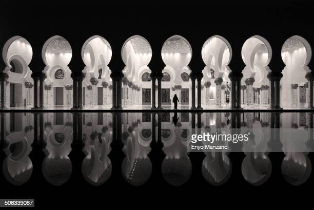 Reflection of columns with Lady in Abaya at Sheikh Zayed Grand Mosque. Black and white. Abu Dhabi UAE