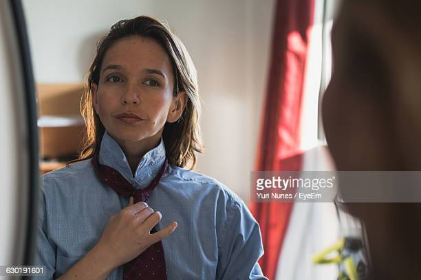Reflection Of Confident Woman Adjusting Necktie On Mirror
